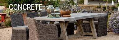 concrete outdoor patio dining table and wicker chairs