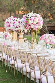 outdoor wedding reception table with gold white damask tablecloth golden chairs with pink cushion