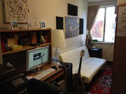 white futon bed by the window and wooden computer desk with shelf in guys dorm room