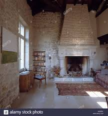 large stone fireplace in country living room with stone walls