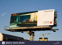 a fine art painting by edward hopper is reproduced on a large commercial billboard over ventura blvd in the san fernando valley area of los angeles