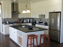 stainless steel kitchen pendant lighting. black quartz countertop kitchen with white wooden cabinet stainless steel refrigerator two pendant lights and lighting