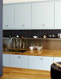 Ice blue kitchen cabinets with routed out handles, solid oak countertop,  stainless steel backsplash and shelf, black hexagonal tiles