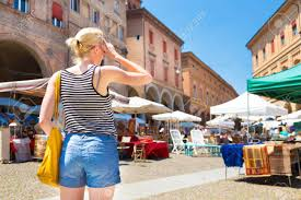 lady walking the flea market on old traditional piazza of santo stefano square of bologna