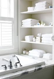 open shelving at end of bathtub in white chic bathroom