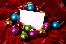 a blank notecard surronded by christmas decoration or baubles a blank notecard surronded by christmas decoration or baubles on a red background add copy