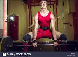 young man doing heavy sumo deadlift exercise in gym club