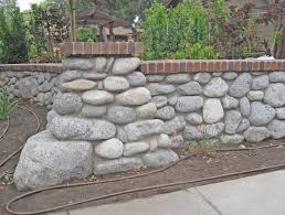 random fieldstone dividing wall with common brick capstone consisting of granite and granitic gneiss cobbles eroded from the san gabriel mountains