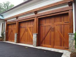 a three car garage has carriage style doors made of chestnut colored wood