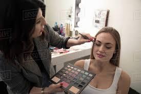female makeup artist applying makeup to model preparing for photo shoot
