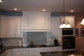 glamorous glazed white kitchen cabinets with white glass tile backsplash and copper kitchen pendant lamp design