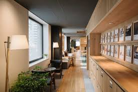 Image Uniqlo Narrow Well Lit Hallway With Plants And Light Wood Filing Cabinets Lining The Walls Airbnb Design Worklife Balanced Airbnb Design