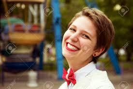夏気分美しい短い髪型の女の子は笑うし手書きのホイールの背景に遊園