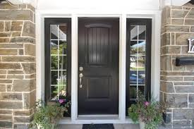 large paned windows frame a matte black door with simple hardware on this stone brick home