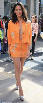 Olivia Munn flashes cleavage in orange jacket and mini Daily.