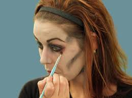 applying eyeliner for zombie makeup