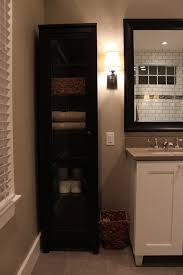 tall black wooden corner linen cabinet with single glass door and four legs