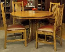light brown wooden round table with single stand combined mission style wood and leather chair