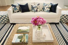 living room with blue and white striped rug white couch with navy and bird printed