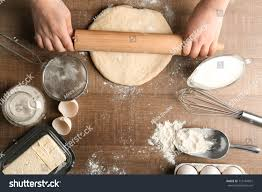 Woman Rolling Dough On Kitchen Table Stock Photo Edit Now