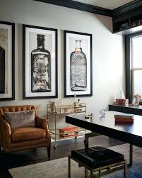 a glass and gold bar cart brown leather armchair and oversized artwork of mens bedroom wall