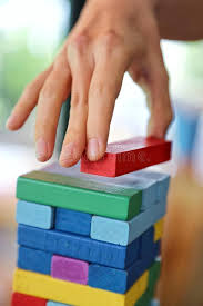 Game Played With Wooden Blocks Closeup Of Woman`s Hand Pick The Red Stack On The Wooden Tower 81
