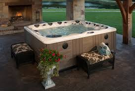 this above ground hot tub is placed on a stone patio and overlooks an open air space with an outdoor fireplace cushioned seating and potted flowers