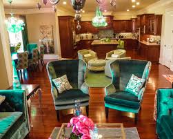a couple velvet wingback accent chairs in open plan kitchen living room and dining room combined with varnished hardwood floor