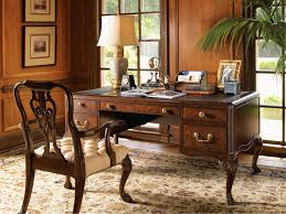 elegant office desk. beautiful elegant artistic carving on solid maple desk and classic wooden armchair  traditional brown carpet facing wood framed glass windows inside elegant home office for a