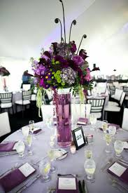 Wedding Table Decor Ideas with Tall Purple Flowers on Purple Glass