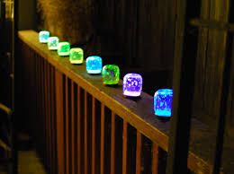 Baby food jars with broken glow sticks inside.
