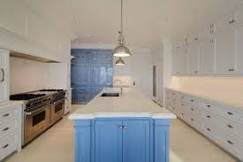 luxury kitchen with blue and white cabinets island with carrara marble counter and subway tile backsplash