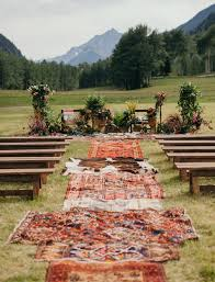 the ceremony spot was decorated with greenery and flowers and covered with rugs that bride had