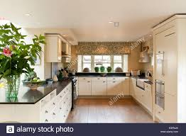 Stylish Kitchen White Units With Black Granite Worktops By Magnet In Stylish