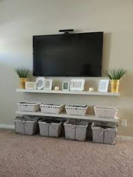 furniture under wall mounted tv. mounted tv on wall with floating shelves below. the wires are routed through into garage where all components are. furniture under tv u