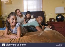 Happy African American family lying on bed watching TV Stock