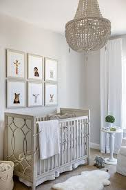 an rh baby child dauphine wood empire chandelier hangs over a sheepksin pelt and lights a gender neutral nursery furnished with an rh baby child vienne