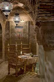 romantic dining room decoration with moroccan style with brick wall great chairs and round dining table with pendant lamp image