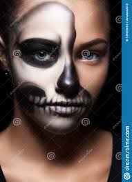 portrait of young beautiful in a black hood skeleton makeup half face