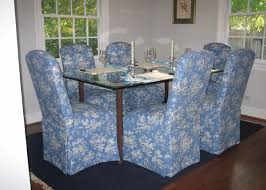 dining room with hatteras skirted parsons chairs around a glass table