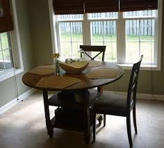 needs by building a round storage dining table this simple plan uses a standard round tabletop standard bun feet and an easy to build storage center