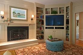corner fireplace with built in bookshelves family room transitional with patterned carpet wall to