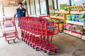 happy trader joe s employee returning ping carts to the outside entrance with woman customer