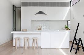 glass tile backsplash by island stone black rimmed steel clerestory windows add illumination in this diminutive white kitchen where black accents
