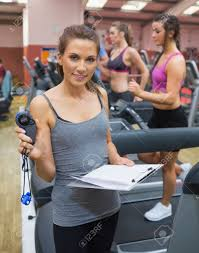 gym instructor female gym instructor holding stopwatch in the gym stock photo