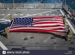 clockwise from top left) Lt. J.P. Vielma, MC2 Austin Ingram, Naval  Oceanography Mine Warfare Center's Lt. Ben Ziemski and AGAN Logan Schwarz  display the American flag aboard USNS Carson City during BALTOPS