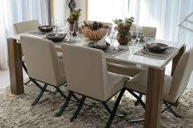 gorgeous marble topped dining table with six place settings fortable soft upholstered chairs and small fl arrangements in a modern home