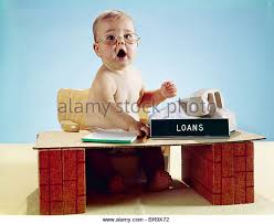 1960s baby businessman sitting at toy desk loans sign wearing eyegl looking at stock