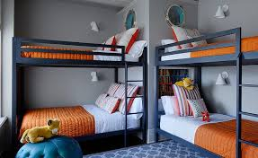 navy blue and orange boys bedroom features two sets of navy bunk beds dressed in white and orange bedding placed under porthole windows which looks into a