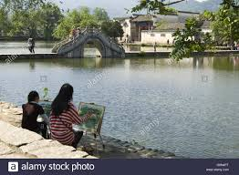 artists painting the famous bridge at hongcun an china